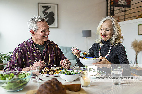 Smiling couple having lunch at dining table