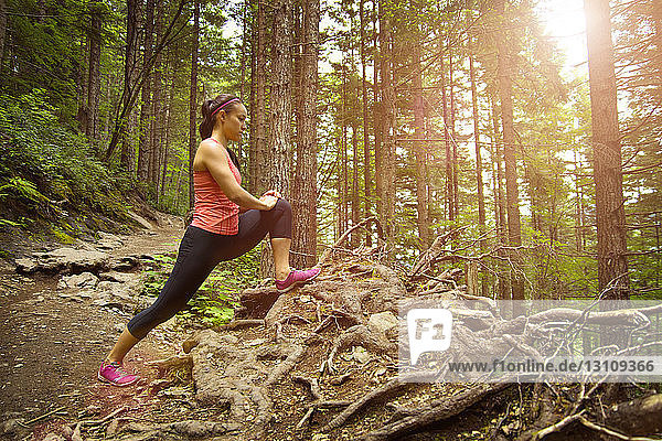 Side view of woman stretching at forest