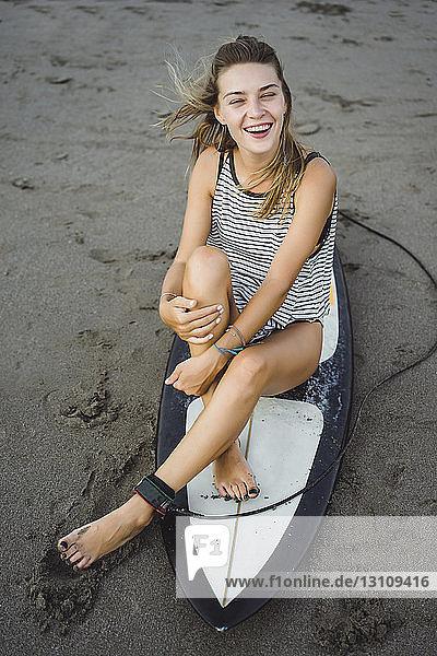 Cheerful woman sitting on surfboard at beach