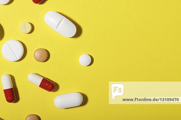 High angle view of various medicines over yellow background