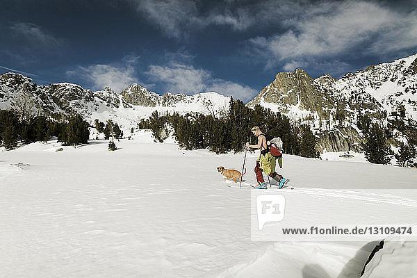 Wanderer mit Hund besteigt schneebedeckten Berg