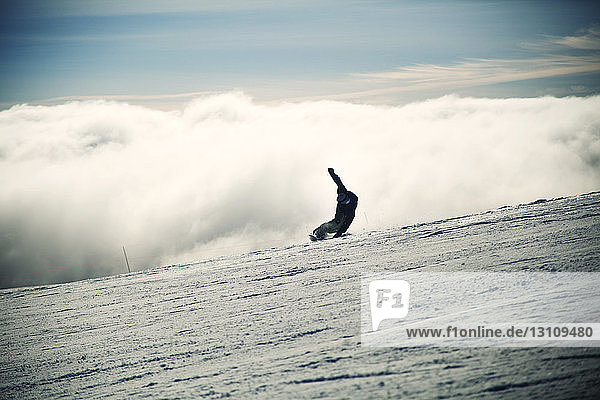 Man snowboarding on snowy landscape during foggy weather