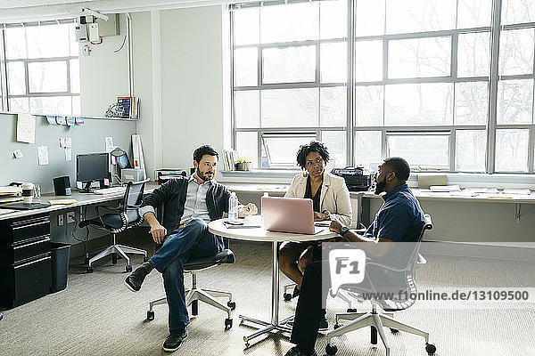 Colleagues looking at businessman explaining during meeting in office