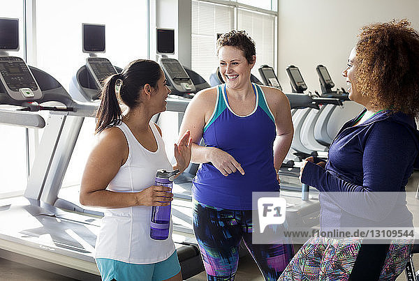 Happy female friends talking while standing in gym
