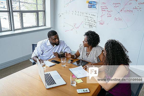 Schrägansicht von Geschäftsleuten  die über Laptop-Computer im Sitzungssaal im Büro diskutieren