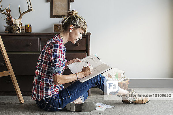 Concentrated female artist drawing in book while sitting at home
