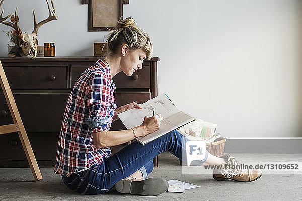 Konzentrierte Künstlerin  die zu Hause sitzend im Buch zeichnet