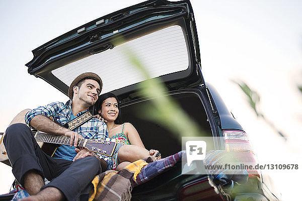 Niedriger Blickwinkel auf das im Auto sitzende glückliche Paar