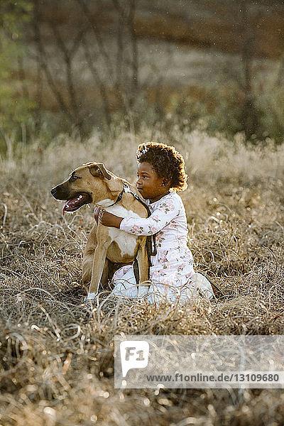 Seitenansicht eines Mädchens mit Hund kniend auf einem Grasfeld im Wald