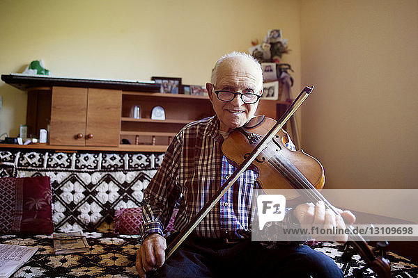 Portrait of senior man playing violin while sitting on sofa at home