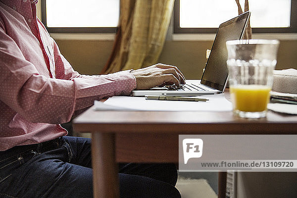 Side view of man using laptop at table