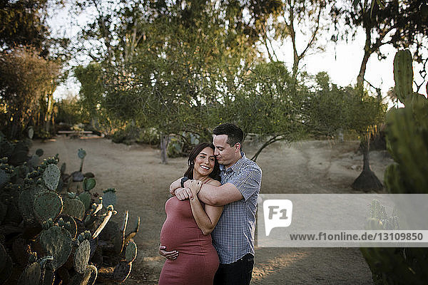 Husband embracing pregnant wife while standing against trees in park during sunset