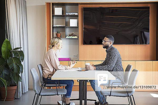 Seitenansicht von Kollegen,  die am Tisch im Büro planen