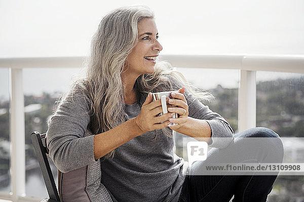Thoughtful mature woman holding coffee mug while sitting on balcony
