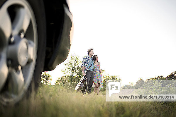 Ehepaar steht auf Grasfeld vor klarem Himmel