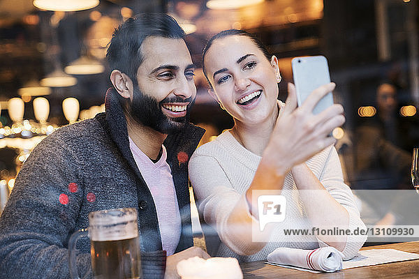 Happy woman with boyfriend using mobile phone seen through restaurant window