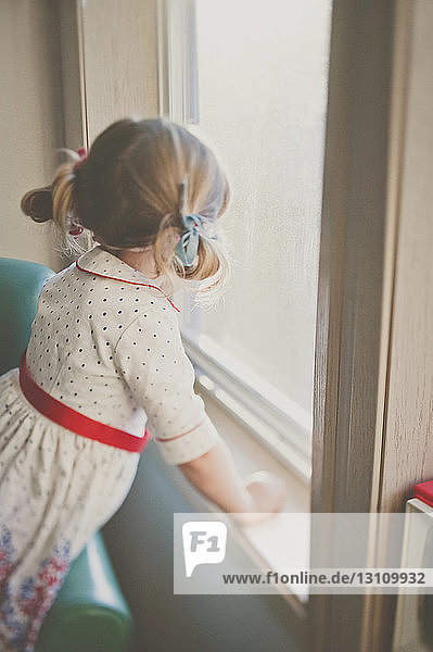 Side view of girl looking through window at home