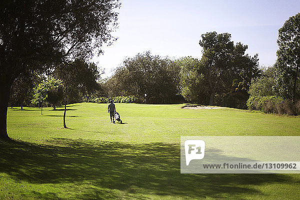 Male golfer walking on golf course against clear sky