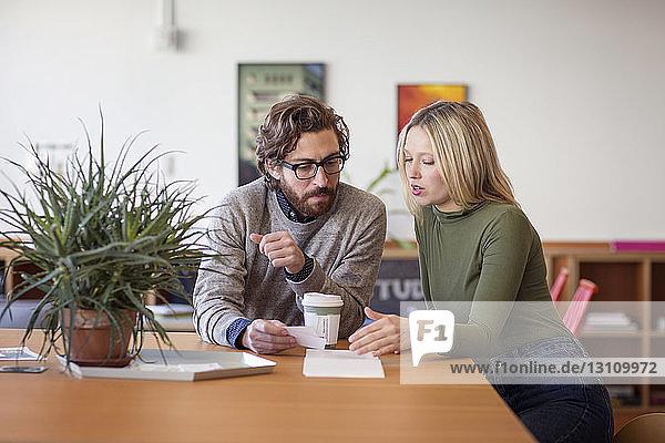 Kollegen diskutieren  während sie im Büro am Tisch sitzen