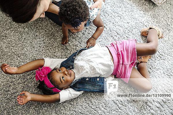 Schrägaufnahme einer Mutter mit Tochter  die das zu Hause auf dem Teppich liegende Mädchen betrachtet