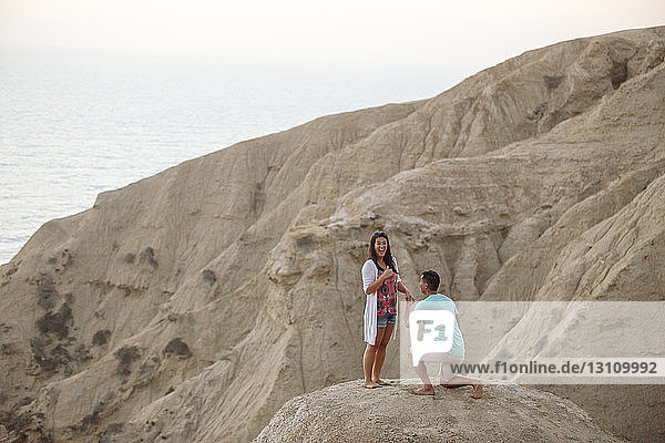 Freund macht seiner Freundin einen Heiratsantrag  während er auf einem Felsen gegen das Meer kniet
