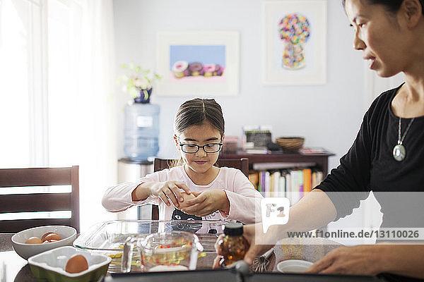 Woman with daughter preparing food at home