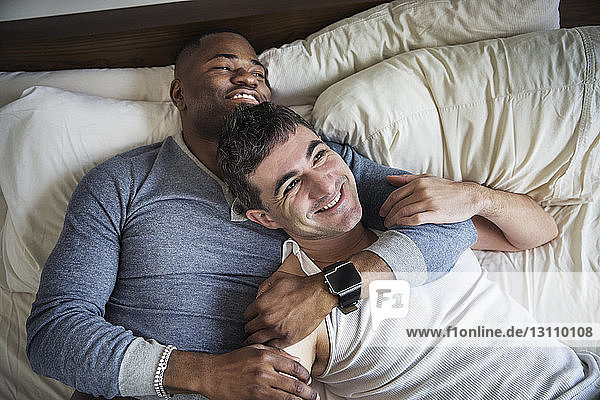 Overhead view of happy loving gay couple lying on bed
