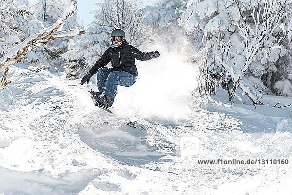 Mann fährt im Winter in voller Länge mit dem Snowboard auf Schnee gegen Bäume
