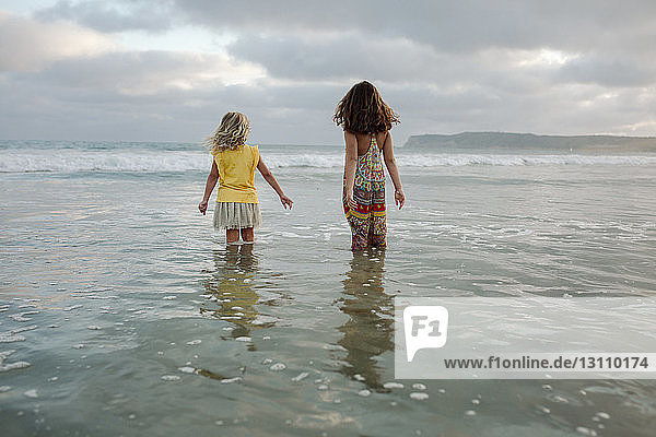 Rear view of sisters standing in sea against cloudy sky