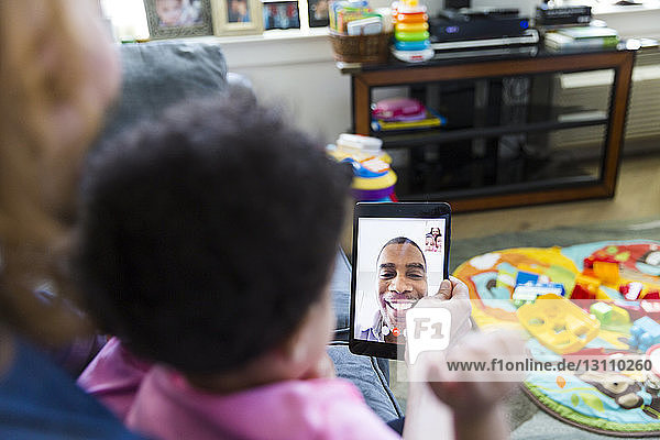 High angle view of mother and daughters video conferencing with father