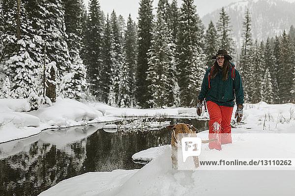 Frau mit Hund beim Spaziergang auf schneebedecktem Feld im Wald