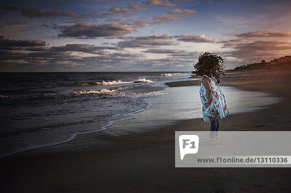Playful girl jumping at beach against cloudy sky