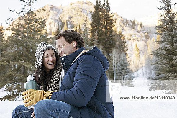 Glückliches Paar hält Kaffee und entspannt sich auf verschneitem Feld