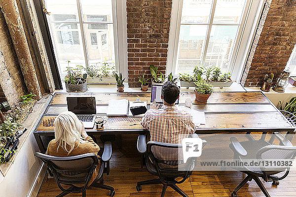 Hochwinkelansicht von männlichen und weiblichen Kollegen  die Laptops am Schreibtisch im Büro benutzen