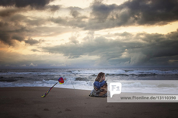 Girl looking at view while being wrapped in blanket on shore against stormy clouds