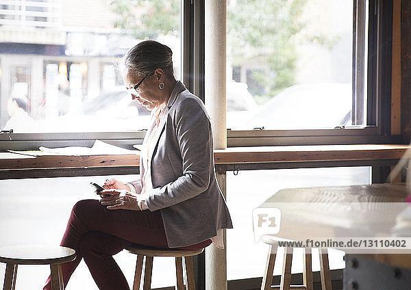 Reife Frau benutzt Telefon  während sie im Café am Tisch sitzt