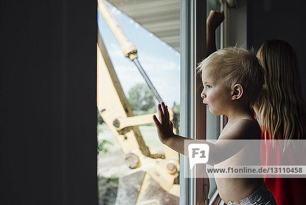 Seitenansicht eines Jungen ohne Hemd  der durch ein Fenster schaut  während er bei seiner Schwester zu Hause steht
