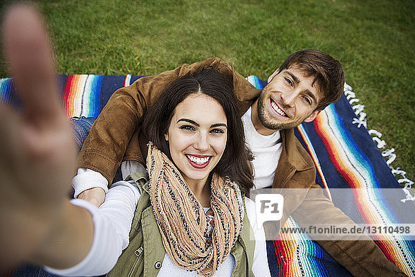 Portrait of happy couple lying on blanket at park