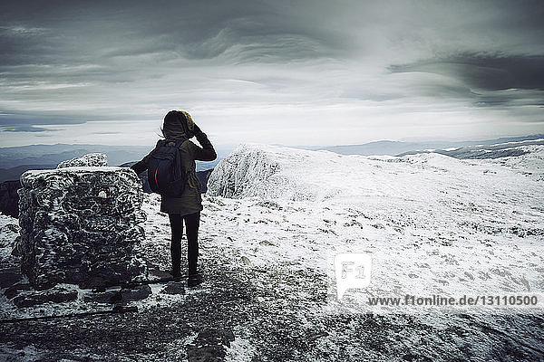 Rear view of woman with backpack standing on snow covered mountain against cloudy sky