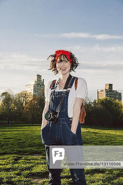 Glückliche Frau mit Händen in den Taschen steht auf Grasfeld im Park gegen den Himmel