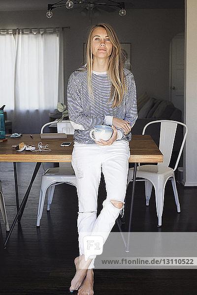 Porträt einer selbstbewussten Frau  die zu Hause steht
