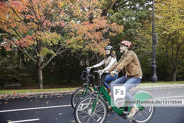 Lächelndes Paar beim Fahrradfahren im Park