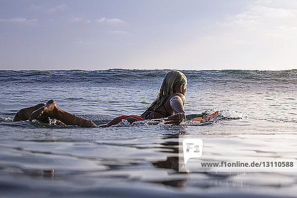 Woman floating on surfboard in sea against sky