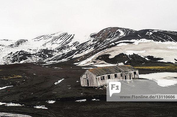 Hochwinkelansicht eines verlassenen Hauses in der Landschaft gegen den Himmel im Winter