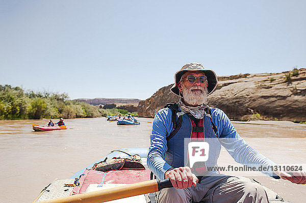 Senior man kayaking in river against clear sky