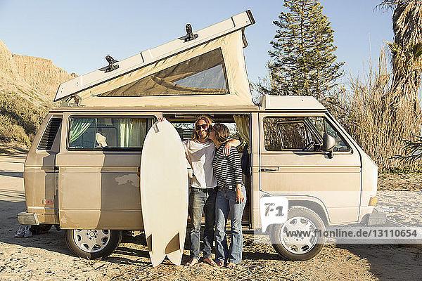 Liebende Frau küsst am Strand des Bundesstaates San Onofre einen Mann  der ein Surfbrett vor einem Kleinbus hält
