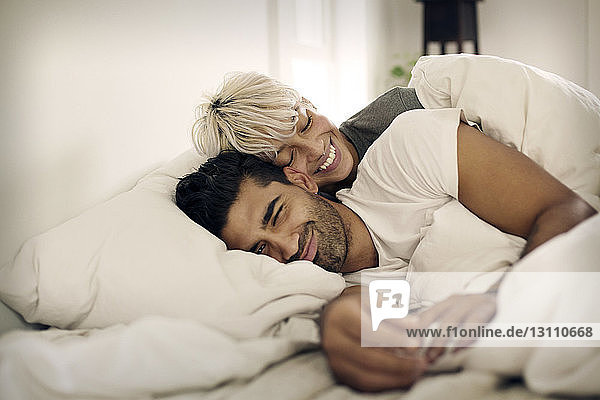 Happy young couple lying on bed at home