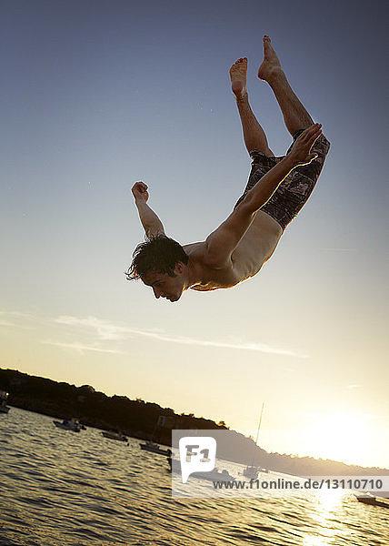 Tiefwinkelansicht eines Mannes  der bei Sonnenuntergang gegen den Himmel ins Meer taucht
