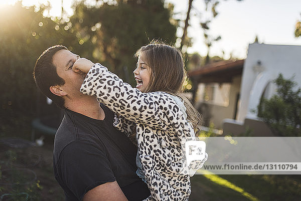 Happy daughter playing with father in yard