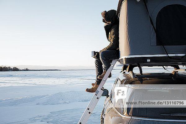 Seitenansicht eines Mannes  der eine Tasse hält  während er im Dachzelt auf einem Auto gegen den Himmel sitzt